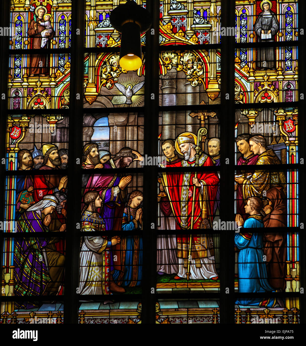 Stained Glass Window depicting Saint Lambertus anointing the Taxandrians during the Confirmation, the rite of initiation. - Stock Image