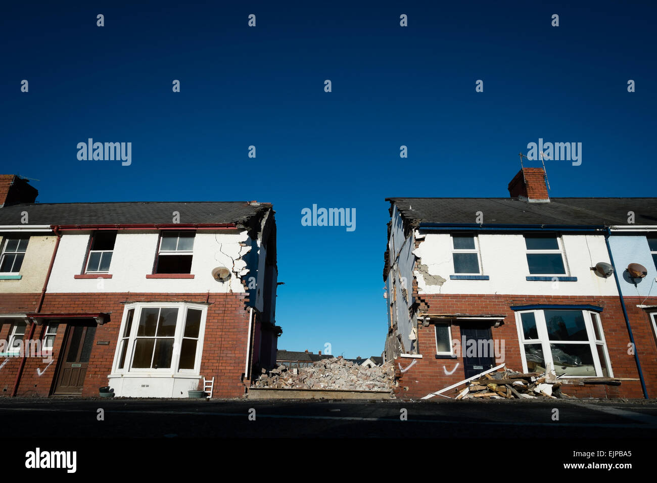 A gap in a terrace of houses where one home has been demolished, UK - Stock Image