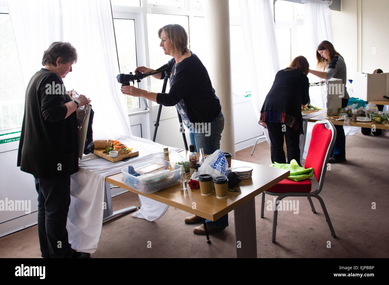 Adult education: Four adult women  setting up their DSLR digital cameras and other props and items in a food photography - Stock Image