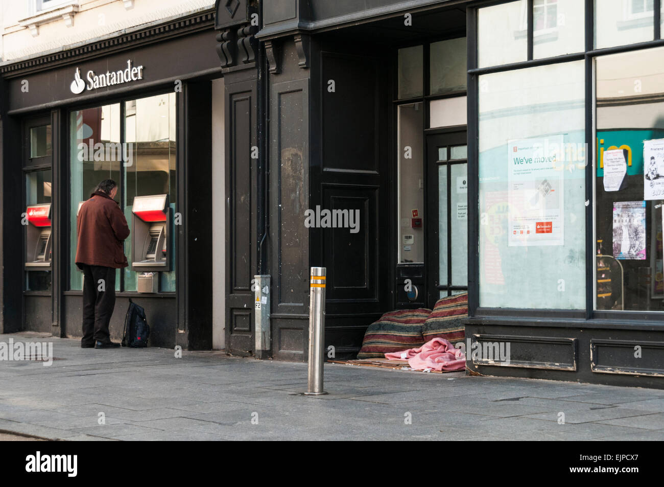 Man withdrawing cash from a bank cash machine next to a homeless persons bed in a disused shop doorway Stock Photo