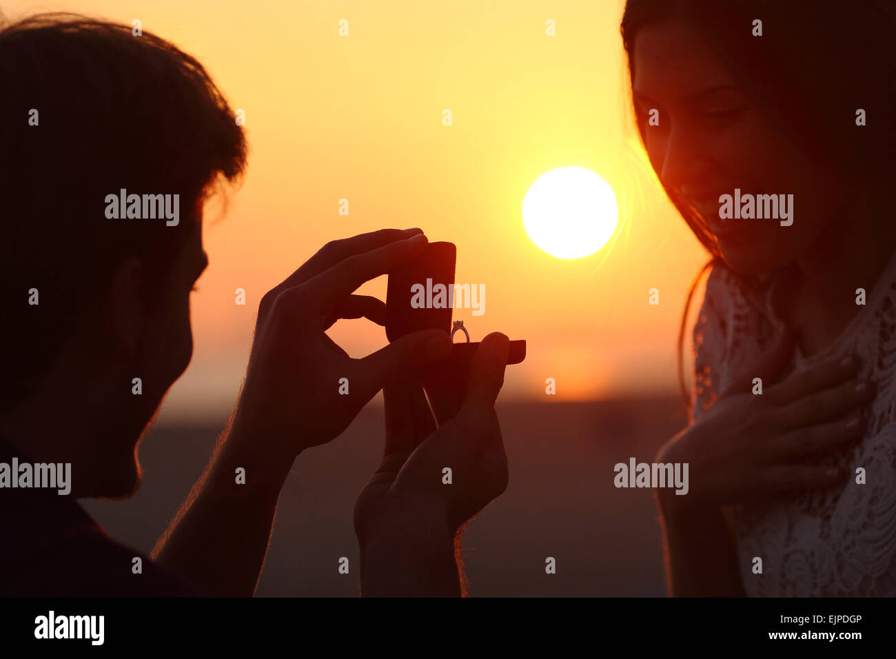 Back light of a couple proposal of marriage on the beach at sunset - Stock Image