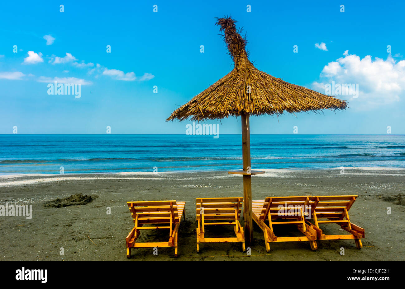 Seaside beach with lounge chairs and straw umbrella. - Stock Image
