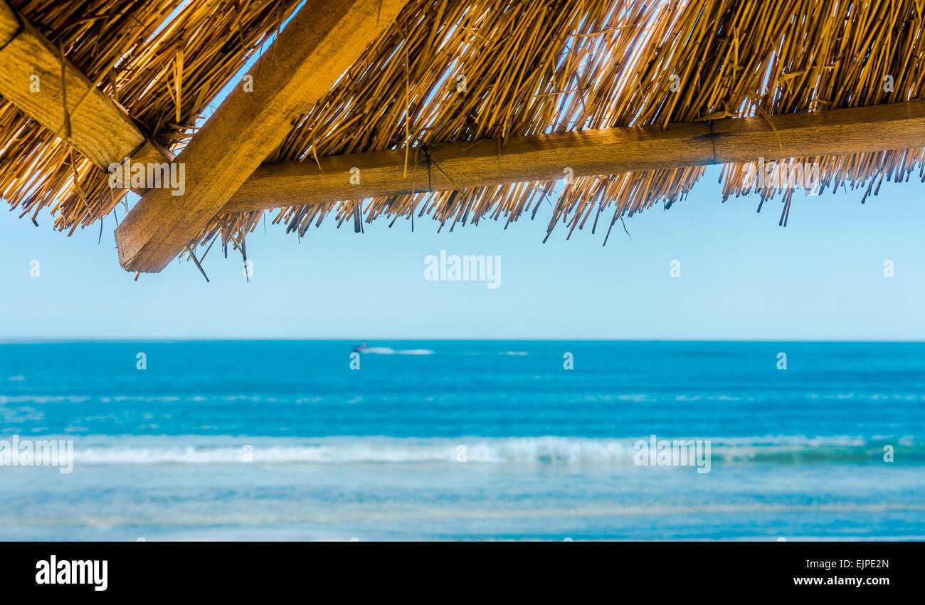 Sea skyline from under straw sun umbrella. - Stock Image