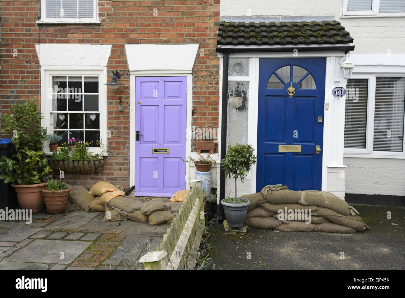 Sandbags piled against house doors during river flood, River Thames, Chertsey, Surrey, England, February 2014 - Stock Image
