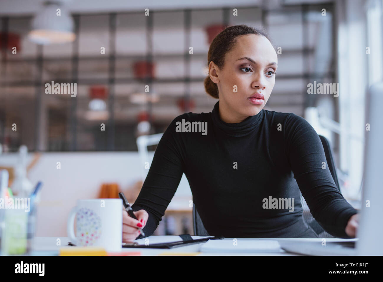 Image of african young woman working new business assignment. Female executive sitting at her desk using laptop - Stock Image