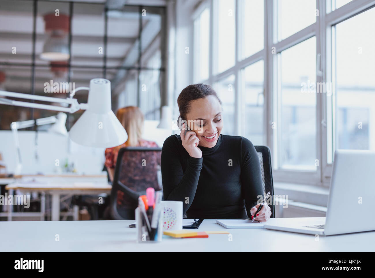 Happy young woman taking notes while talking on mobile phone. African woman working at her desk answering a phone - Stock Image