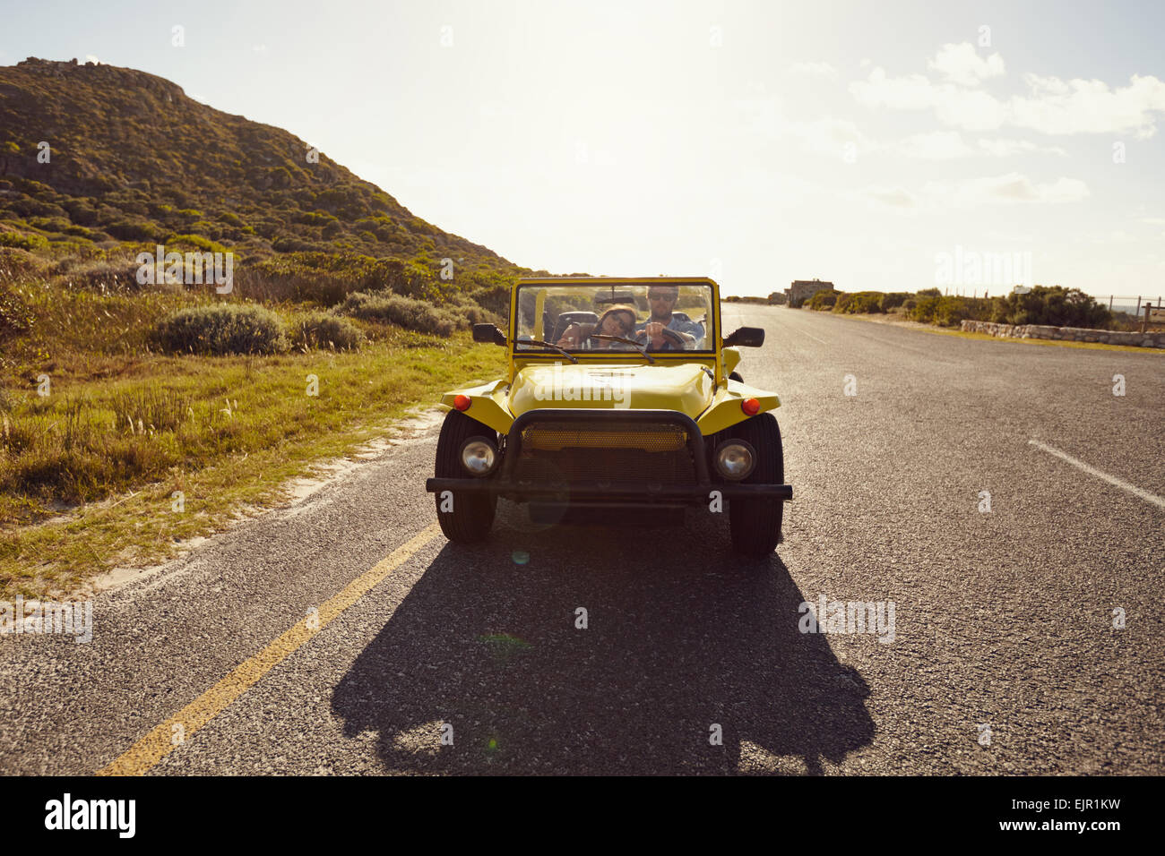 Loving couple driving in a small open topped vehicle on a summer day. Young couple on road trip in a car. - Stock Image