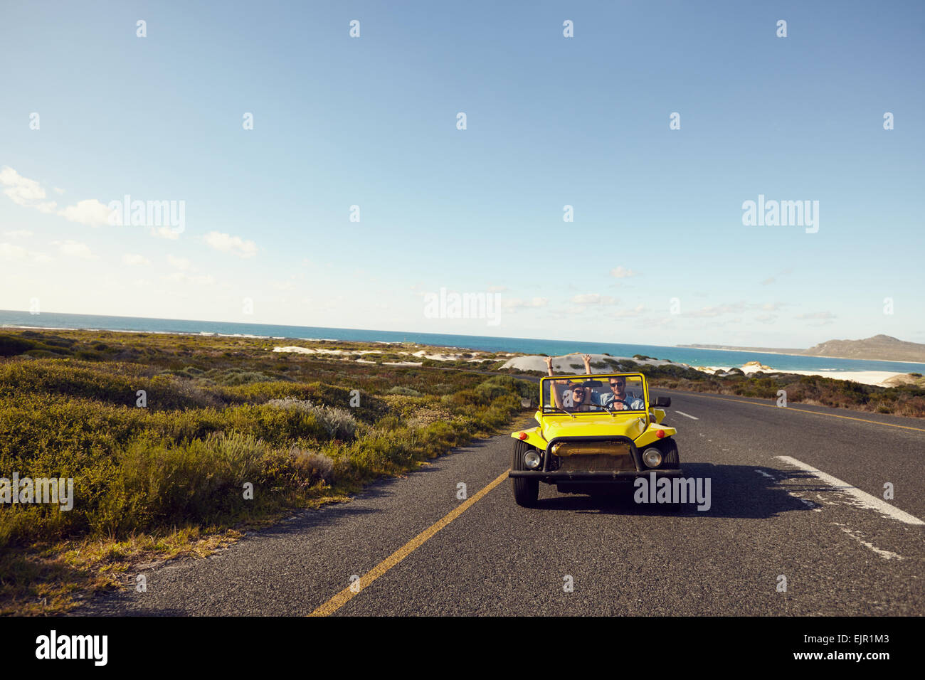 Young couple driving down an open road excited to be on a roadtrip. Happy couple driving a car with their arms raised. - Stock Image