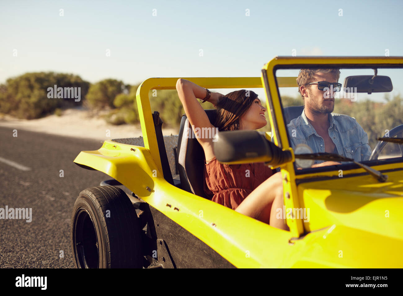 Romantic young couple on a road trip in a car. Caucasian young man and woman going on a holiday in a car. - Stock Image