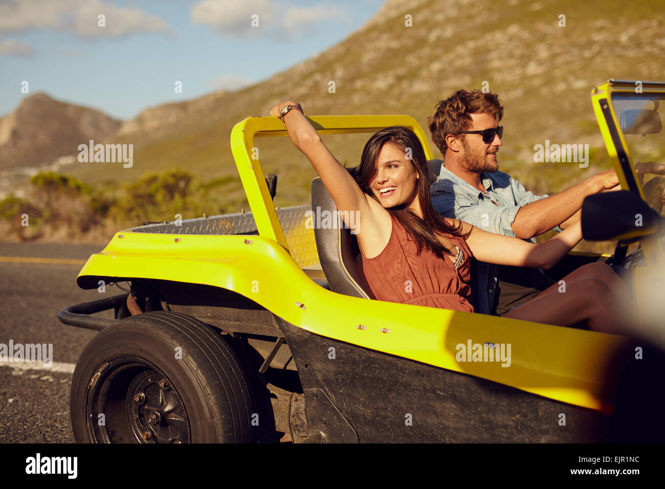 Relaxed couple enjoying in the car ride. Beautiful young woman looking at a view with her boyfriend driving the - Stock Image