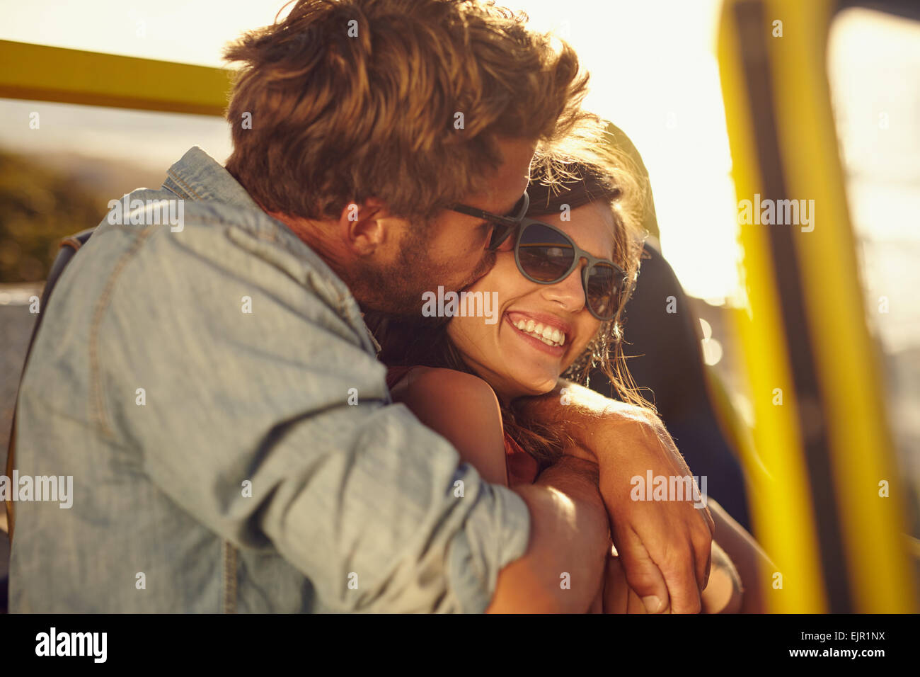 Young man embracing and kissing his beautiful girlfriend while on a road trip. Romantic couple in a car on summer - Stock Image