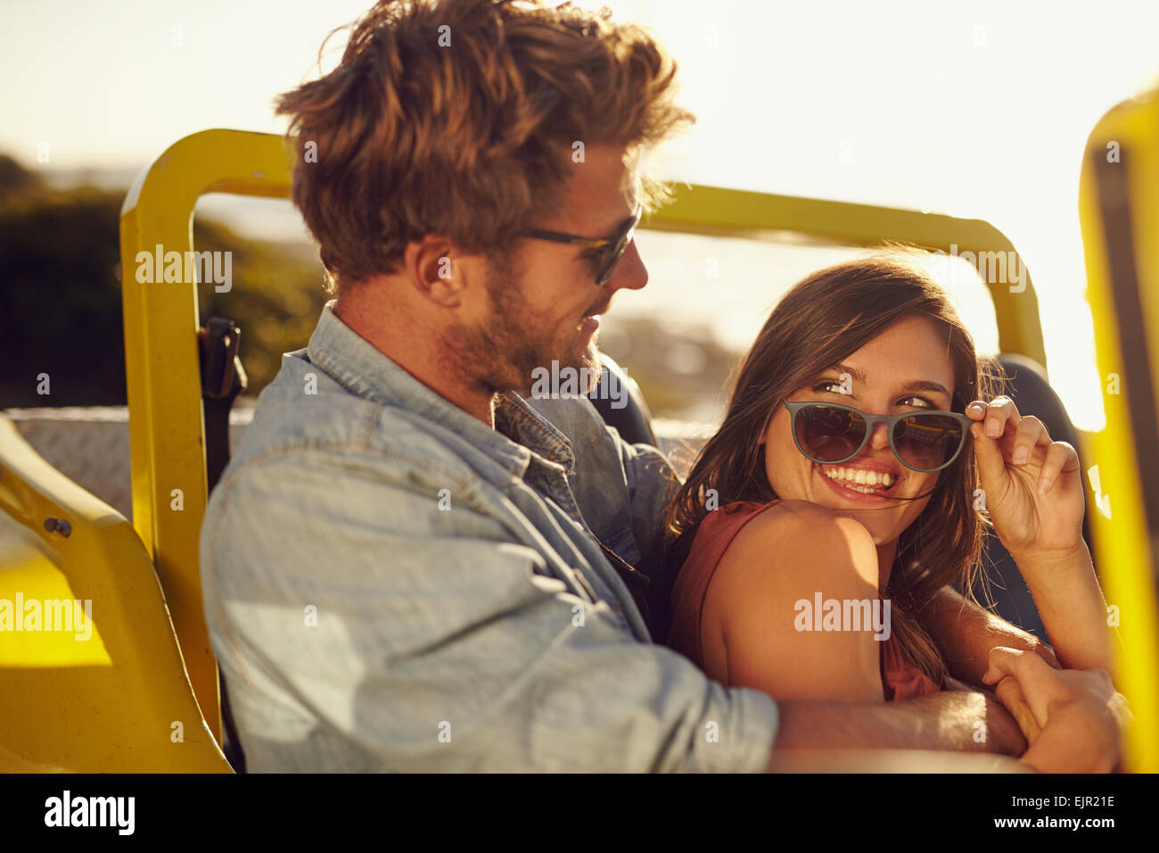 Portrait of romantic young couple having fun on a road trip. Playful young man and woman in a car on holiday. - Stock Image