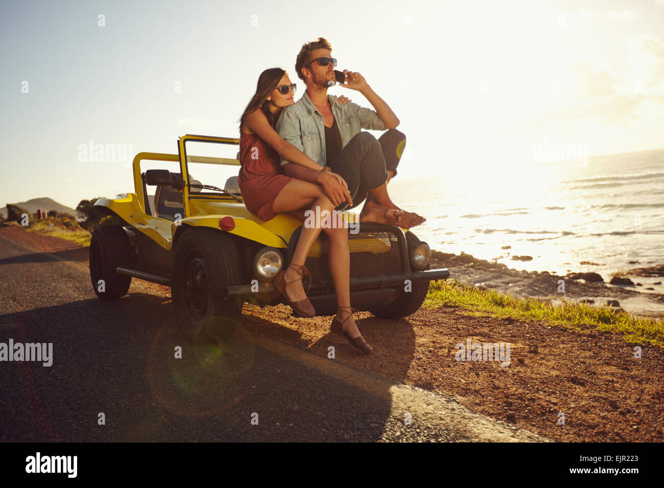Portrait of young couple sitting on a their car by the sea shore, with man using mobile phone. Couple on summer - Stock Image