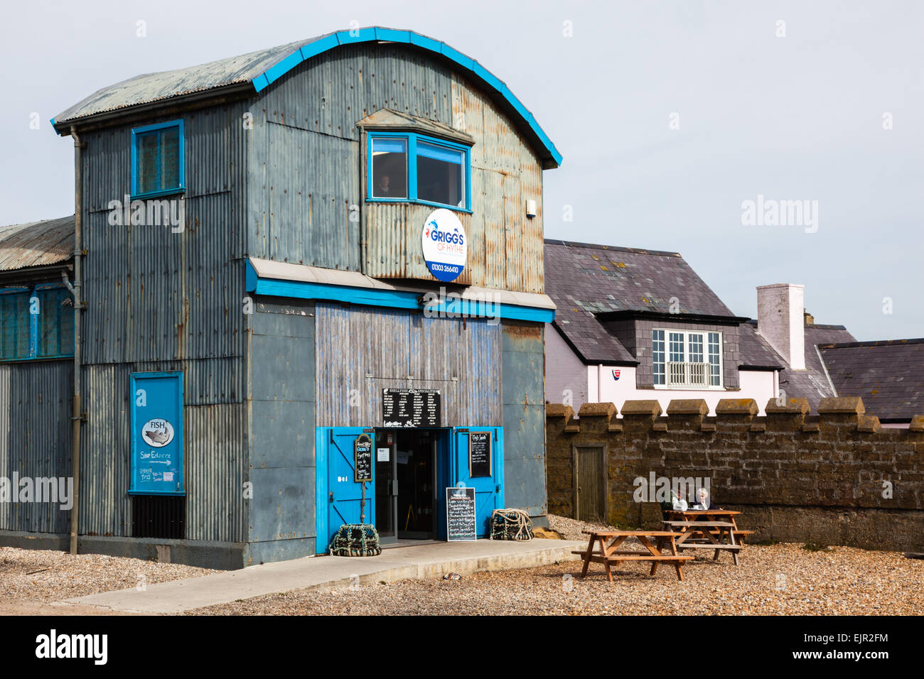 Elderly couple enjoy a hot drink outside a fish cafe and shop on Hythe beach, Kent, UK - Stock Image