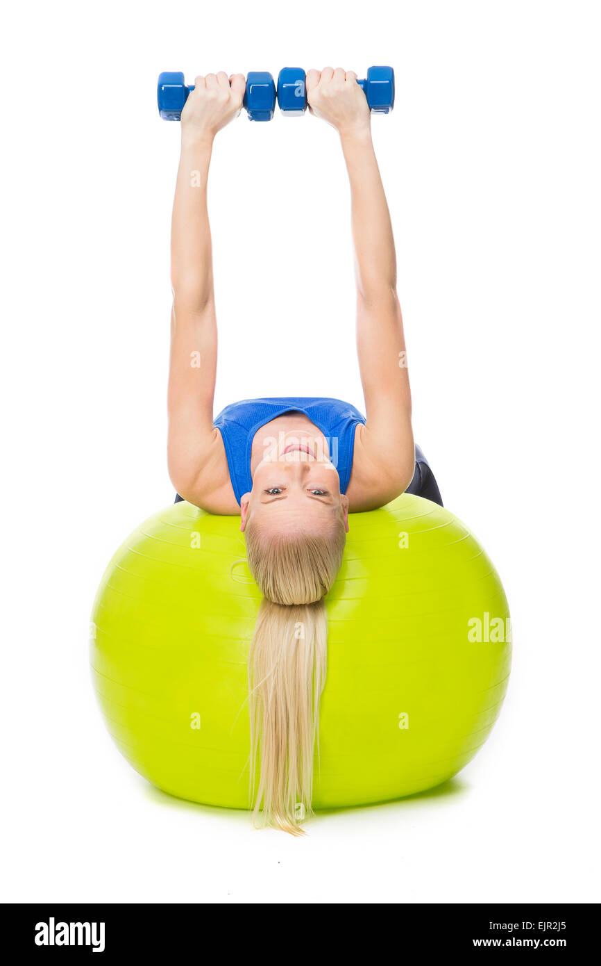 blonde woman wearing fitness clothing exercising with weights on a yellow ball - Stock Image