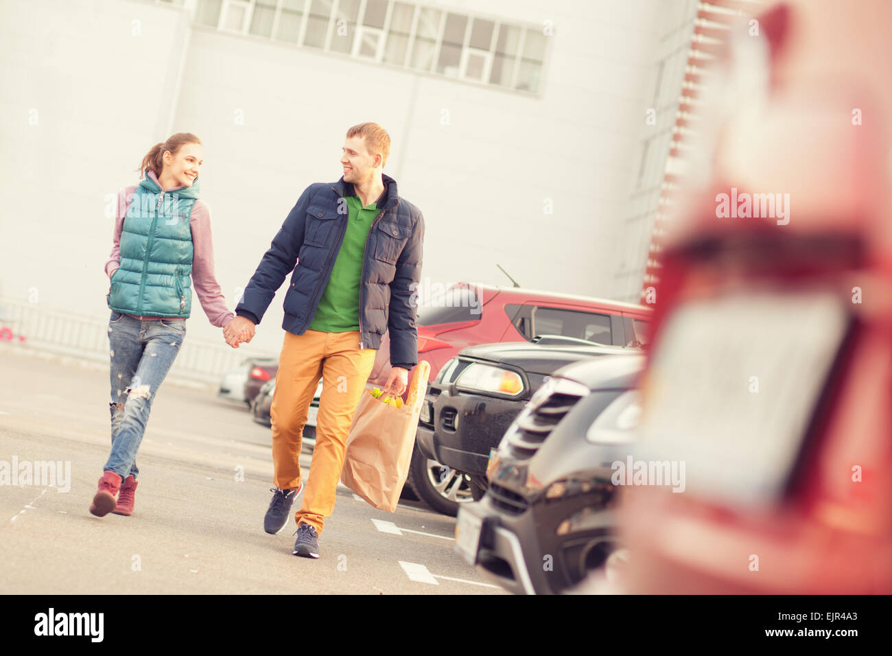 Couple walking on parking after shopping - Stock Image
