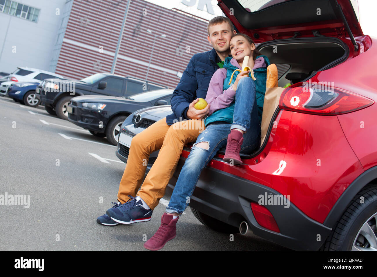 Young couple sitting at car trunk after shopping - Stock Image