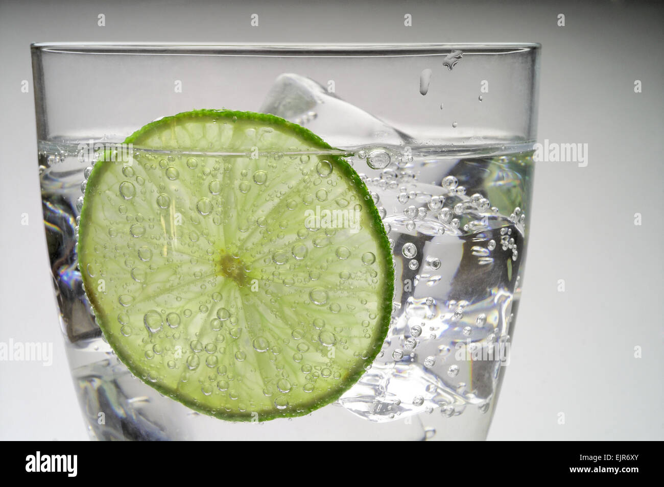 Glass of water with ice and  lime slice - Stock Image