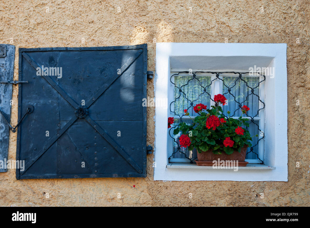 kleines vergittertes Fenster mit roten Geranienstock und eisernem Fensterladen in gelber Hauswand, Pürgg, Steiermark, - Stock Image