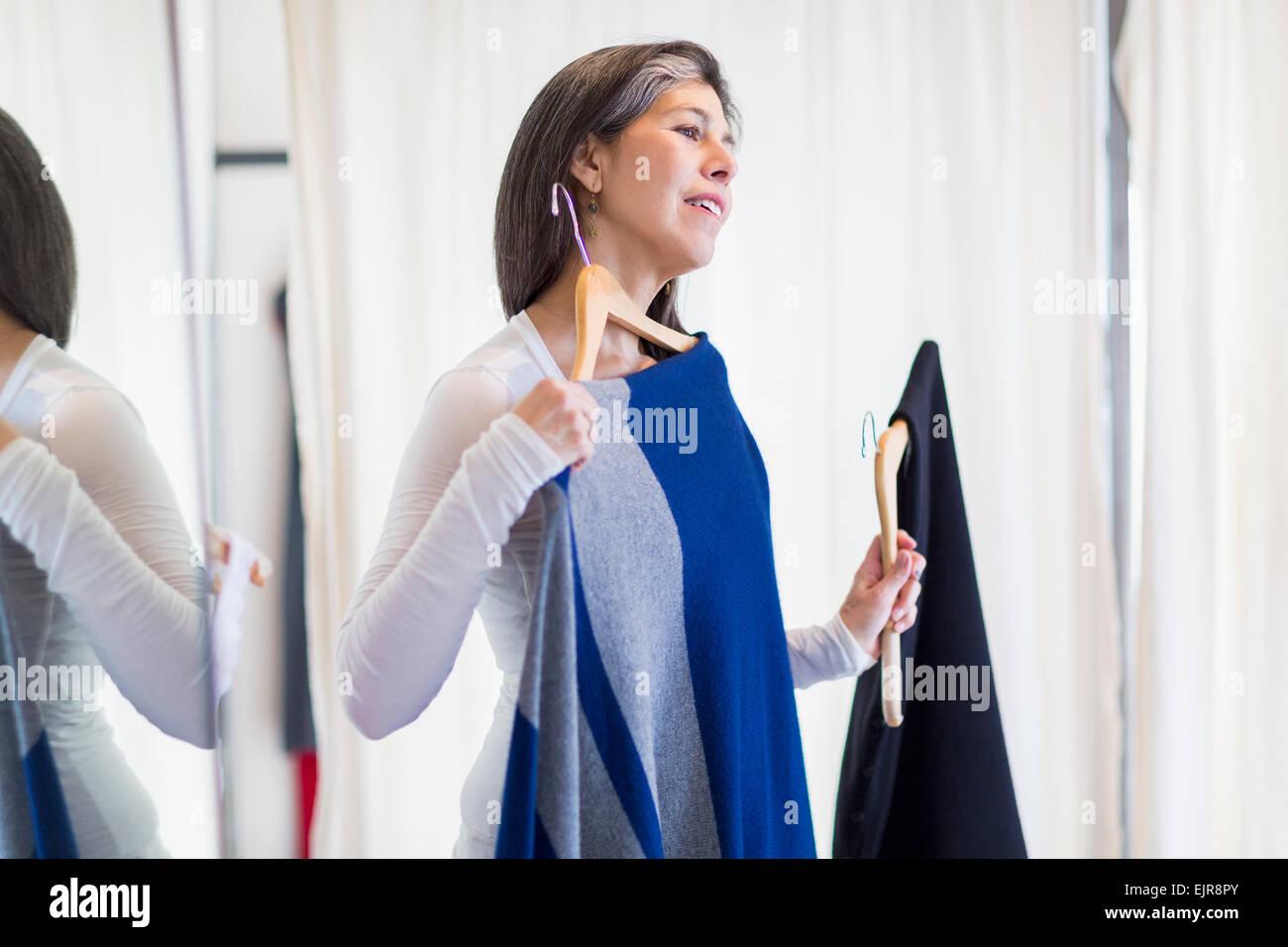 Hispanic woman browsing clothing in store Stock Photo