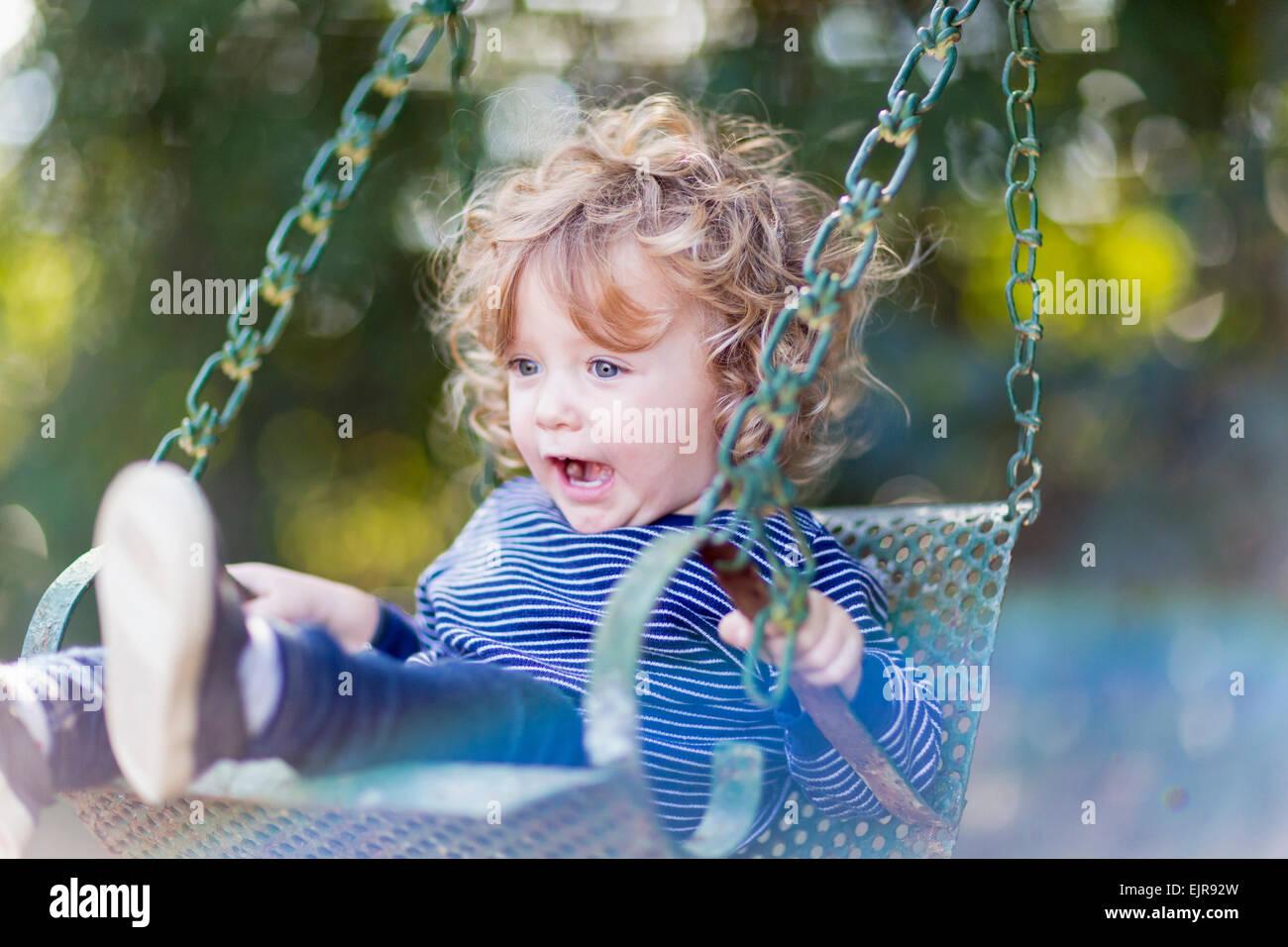 Caucasian baby boy sitting on swing Stock Photo