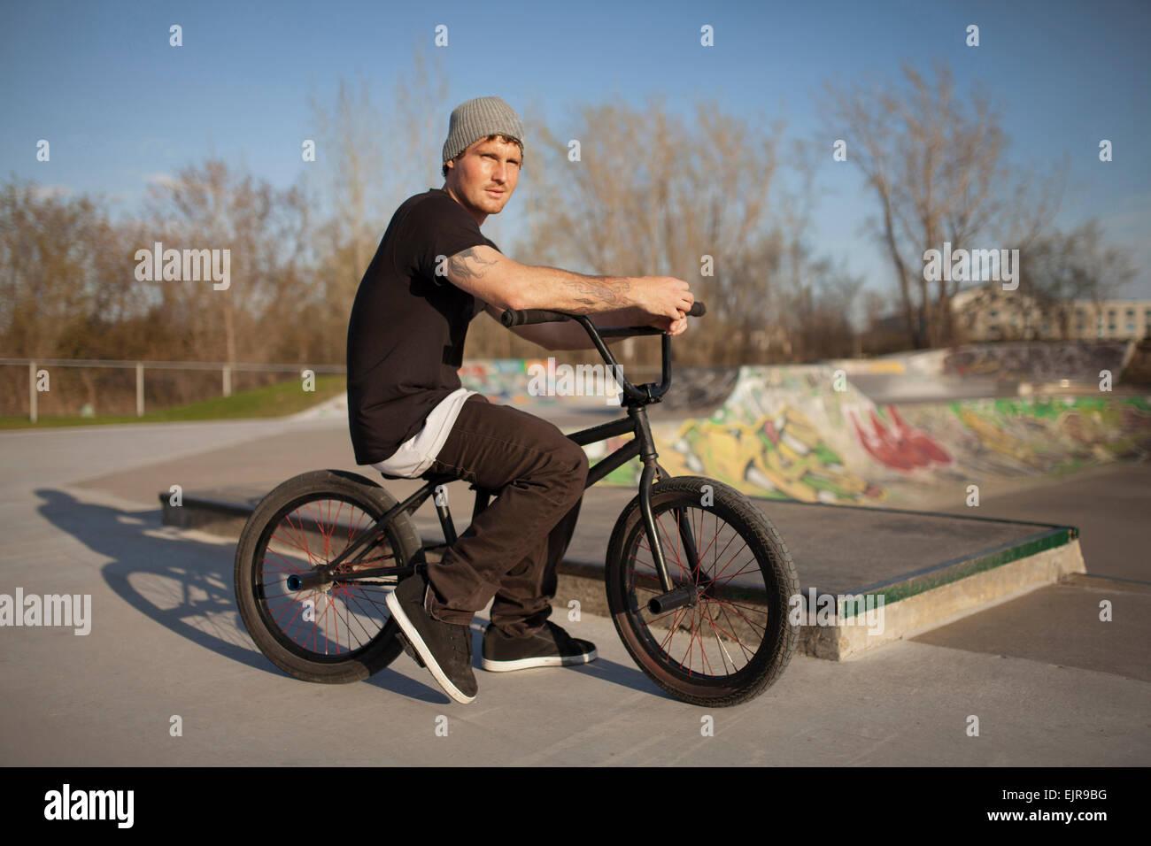 Caucasian man riding BMX bicycle at skate park - Stock Image