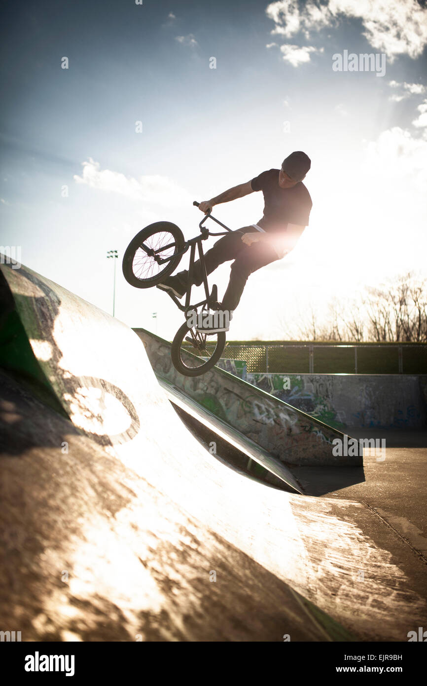 Caucasian man riding BMX bicycle at skate park - Stock Image