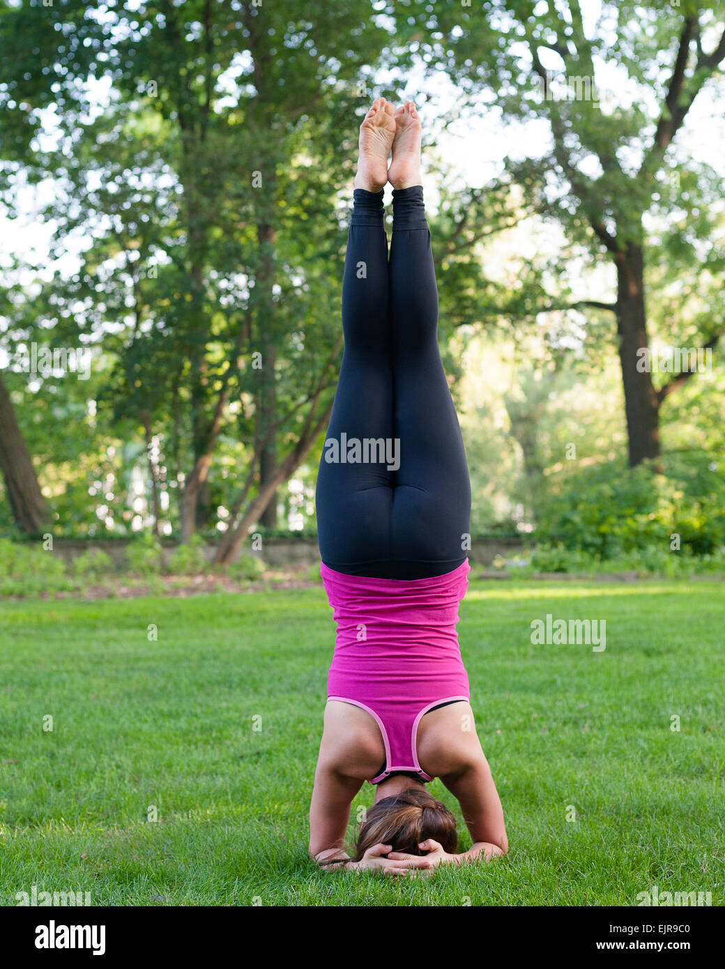 Caucasian woman practicing yoga in park - Stock Image