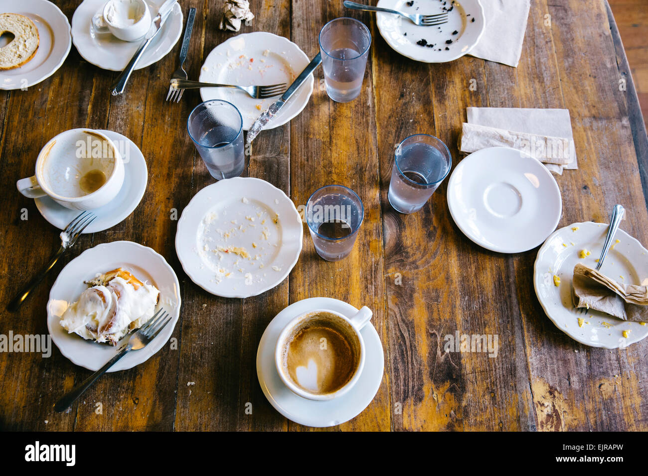 Empty plates, coffee cups and glasses on cafe table Stock Photo