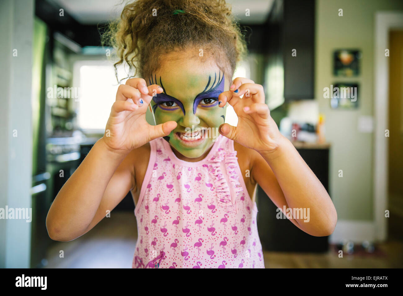 Mixed race girl growling with face paint Stock Photo