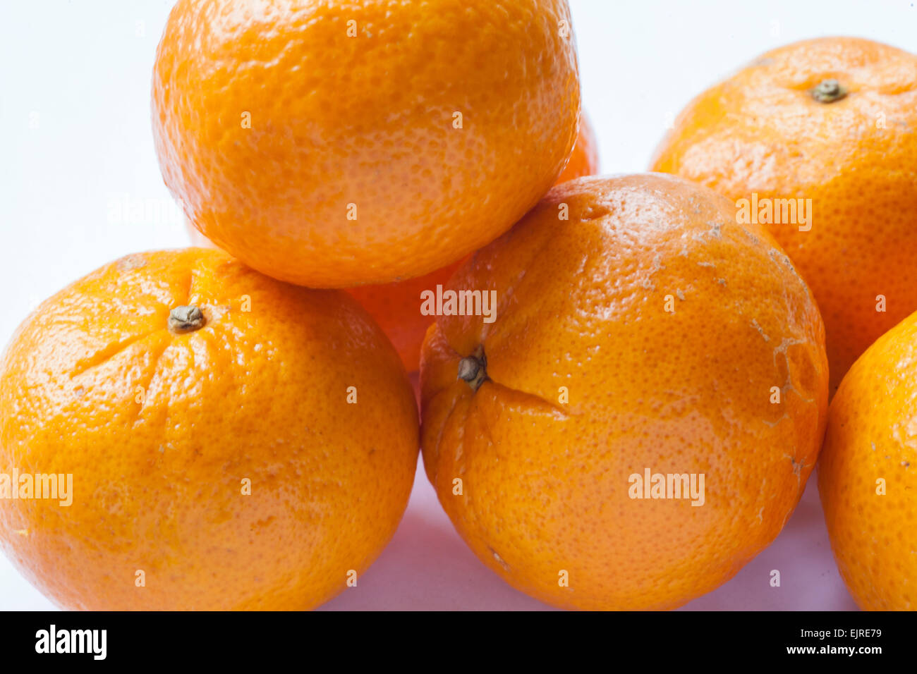 a group of fresh oranges on a clean white background - Stock Image
