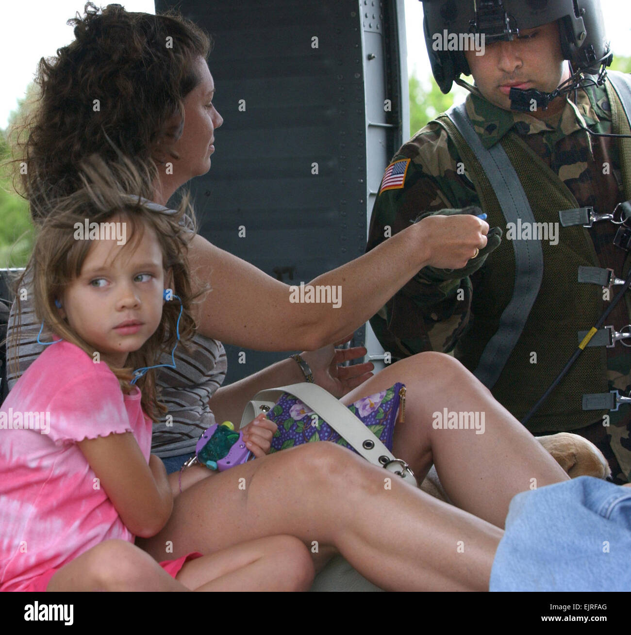 A girl and her mother prepare to be evacuated aboard a Texas Army National Guard UH-60 Blackhawk helicopter from - Stock Image