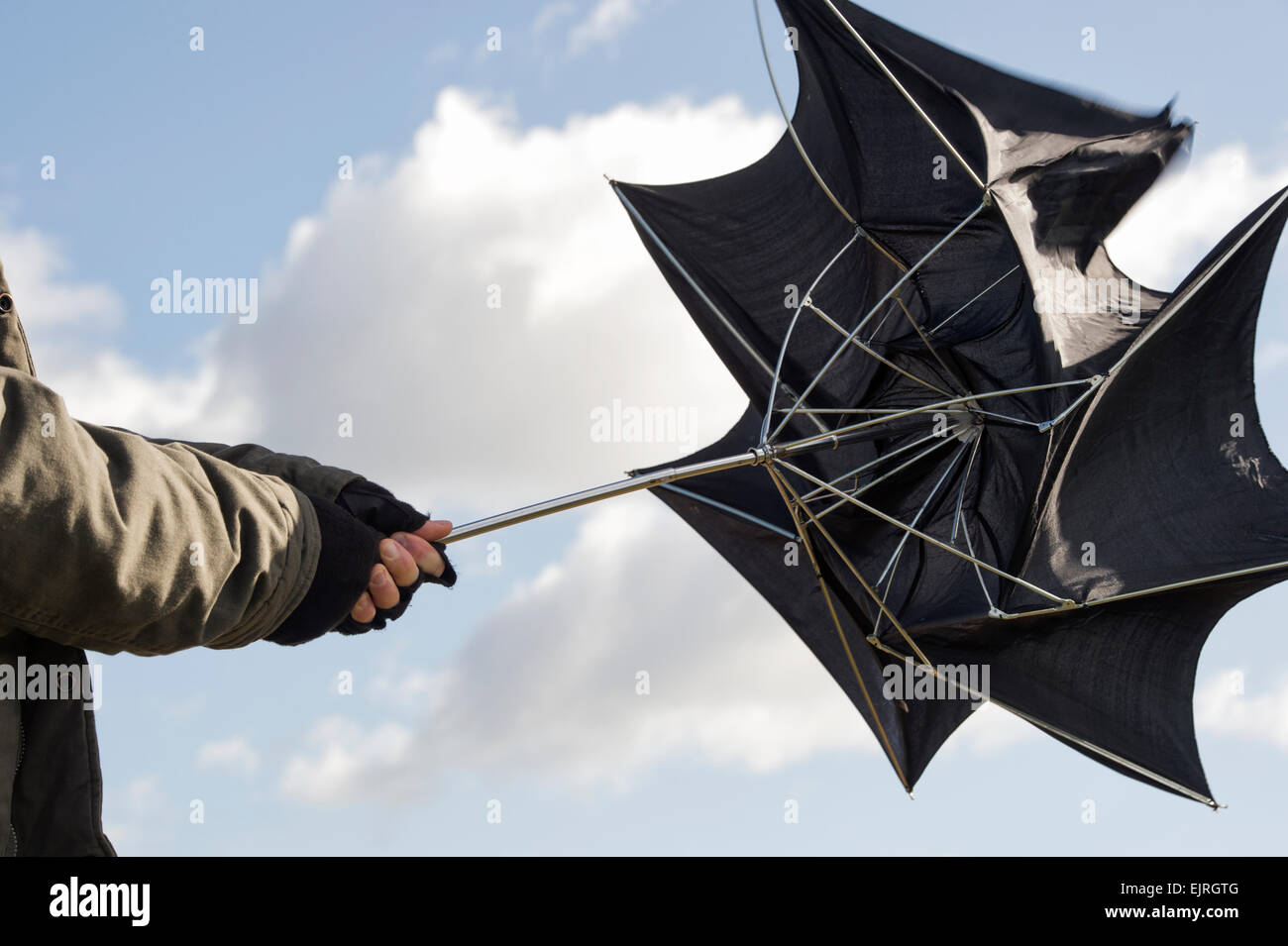 Man holding an umbrella in gale force winds - Stock Image
