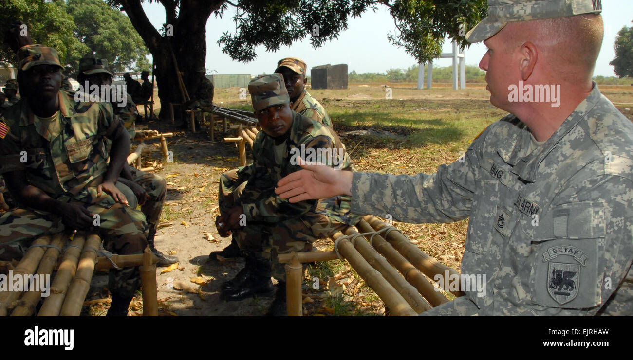Under the shade of a mango tree, Sgt. 1st Class Eddie King, a U.S.   Army Africa NCO, discusses the leadership development - Stock Image