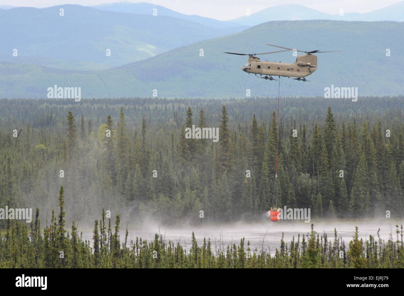 Chinook from Bravo Company 1-52nd AVN BN has just refilled a Bambi Bucket at a local dip sit, the unit is supporting Stock Photo