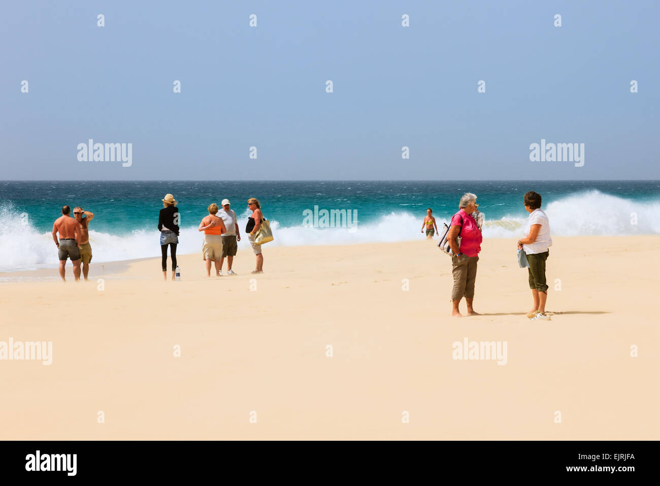 Tourists on sandy beach with rough sea beyond at Praia de Santa Monica, Boa Vista, Cape Verde Islands, Africa - Stock Image