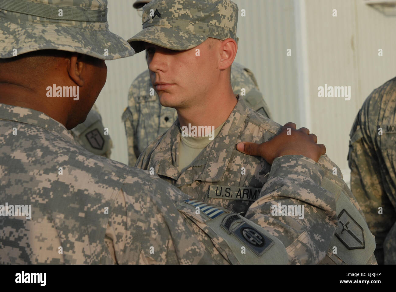 U.S. Army engineer Cpl. Kyle Morris, right, assigned to 46th Engineer Battalion, receives a certificate of achievement - Stock Image