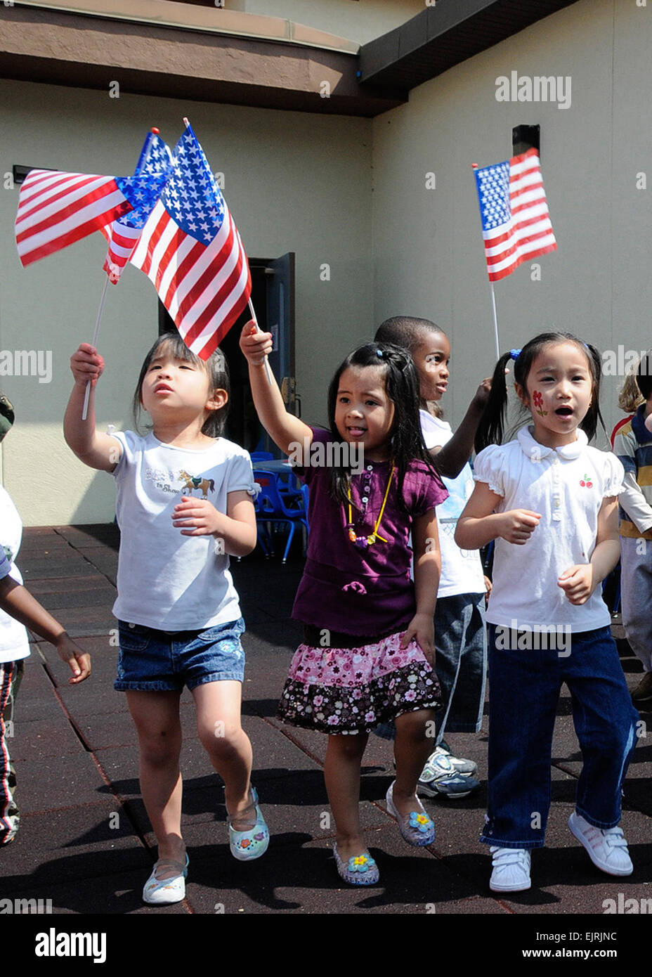United States Army Garrison Daegu, South Korea Child Development Center students march and wave American flags during Stock Photo