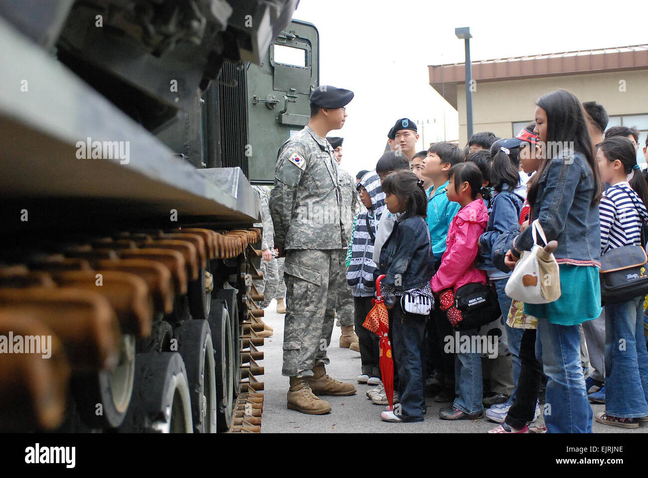 Cpl. Lee, Eui Jong, Co. B., 6th Bn., 37th FA, explains to Wangnam Elementary School students what an MLRS is and - Stock Image