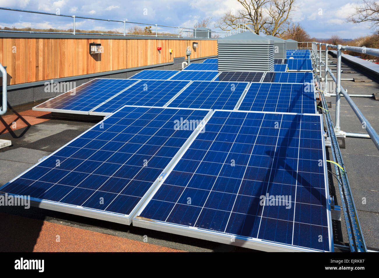 Row of photovoltaic cells on roof of modern  college building - Stock Image