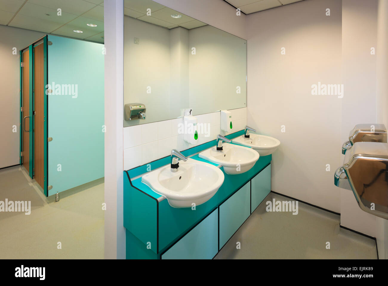Wash basins, hand dryers and toilet cubicals of modern restroom ...