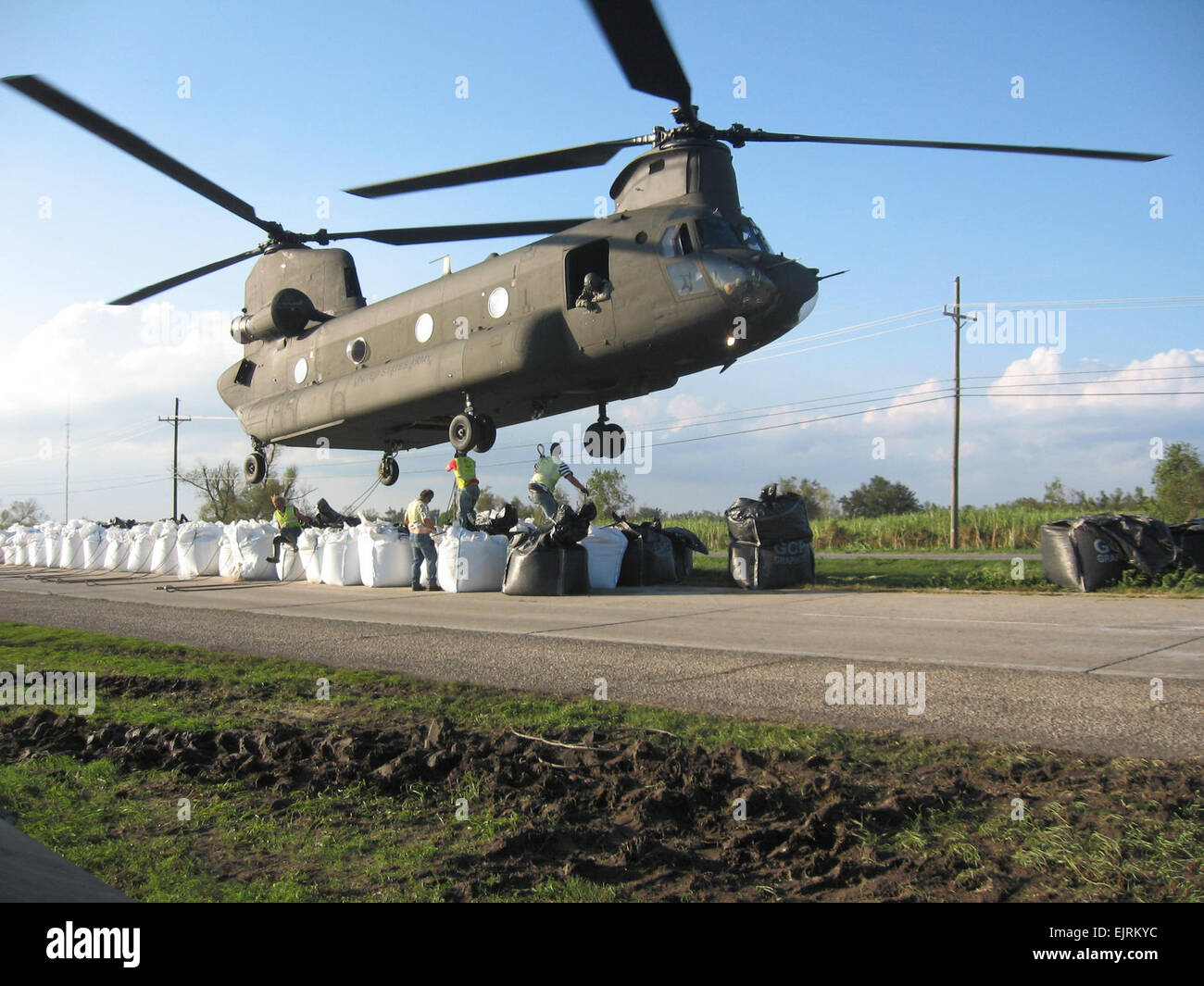 Sandbags weighing 4,000 pounds each are hooked to an Army National Guard CH-47 Chinook helicopter to repair a broken Stock Photo