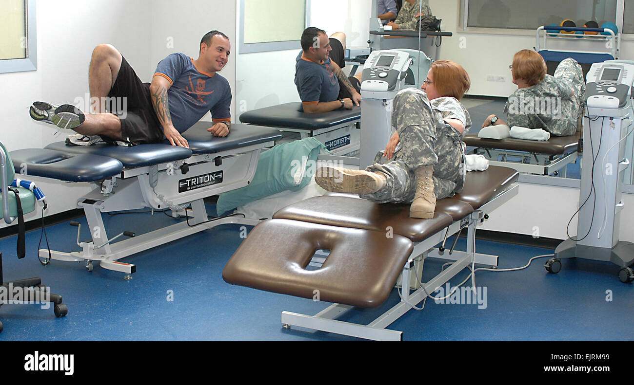 Spc. Jlynn Johnson right, U.S. Army Health Center Vicenza physical therapy clinic technician, demonstrates an exercise - Stock Image