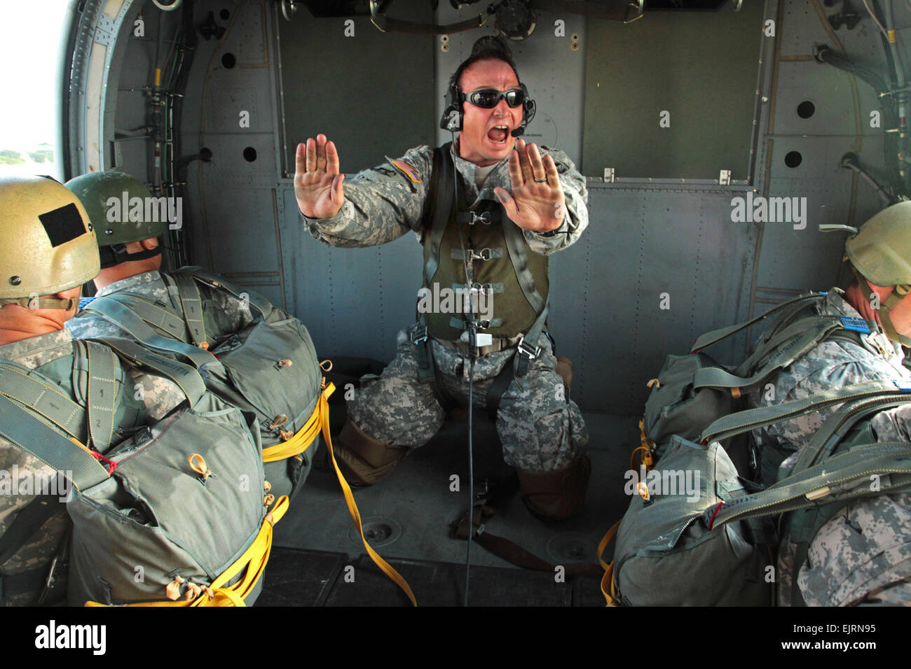 Sgt. 1st Class William Baker, a jumpmaster assigned to Special Operations Command South, yells instructions to paratroopers - Stock Image