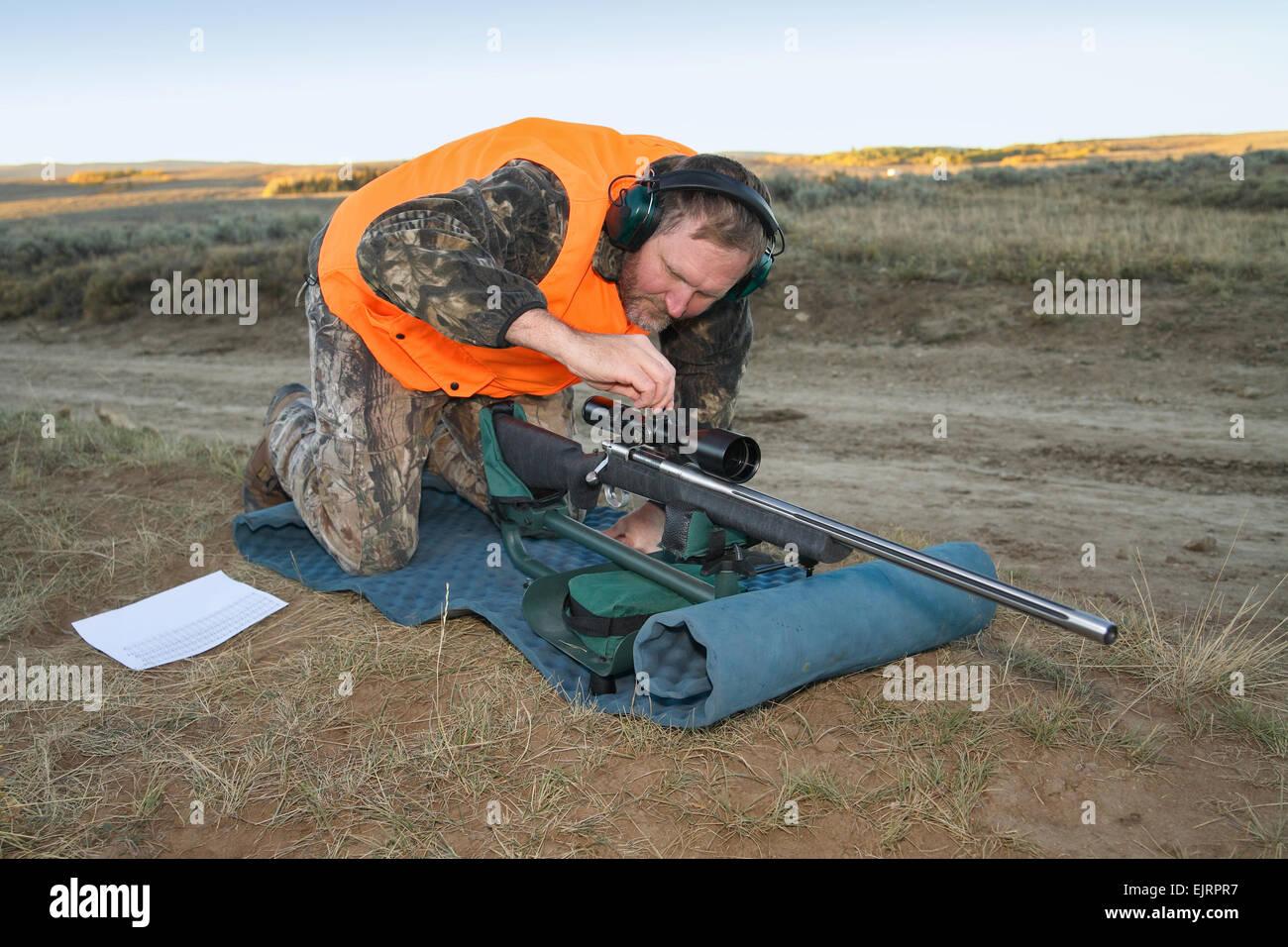 rifle hunter adjusting rifle scope - Stock Image