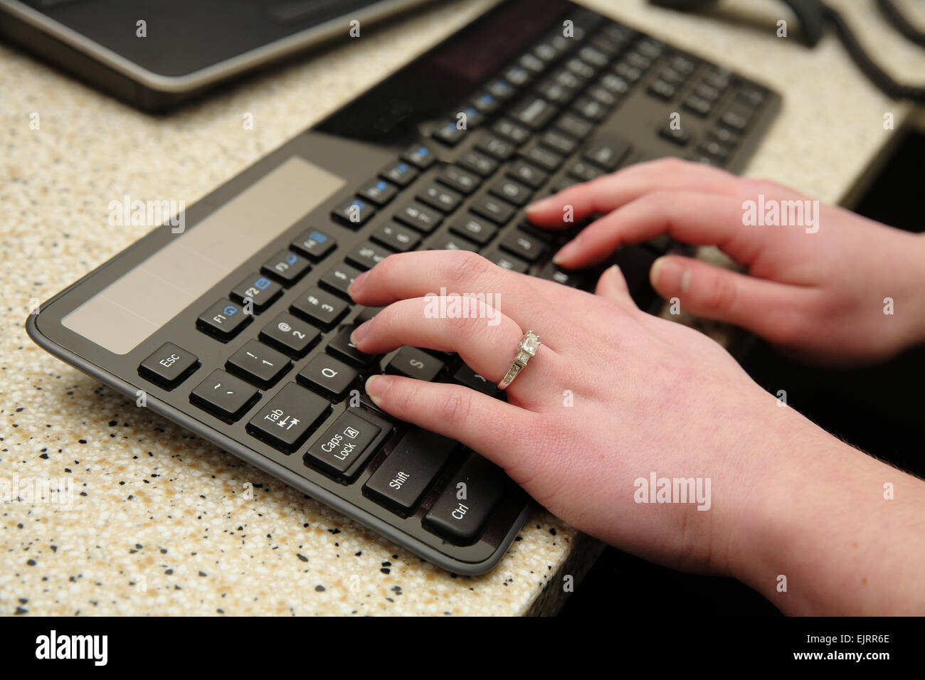 closeup of woman's hands typing on modern keyboard - Stock Image