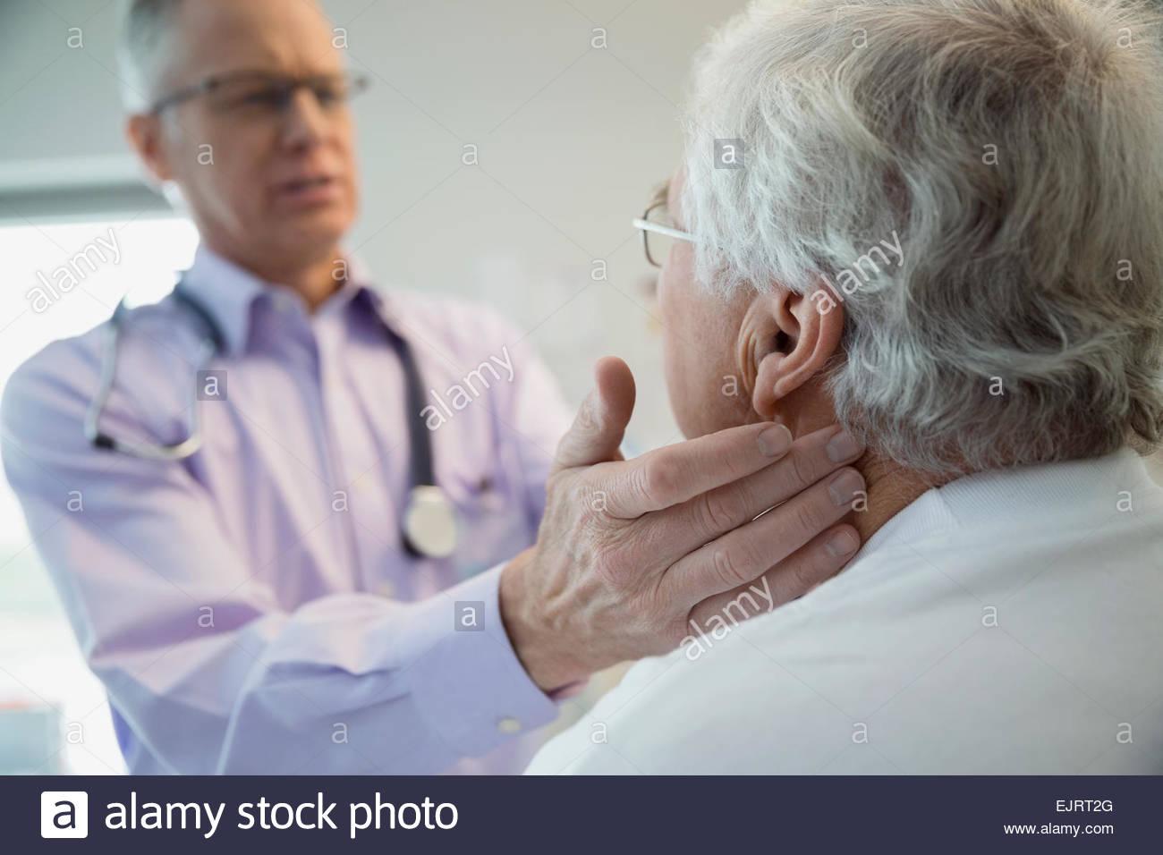 Doctor checking senior mans glands Stock Photo