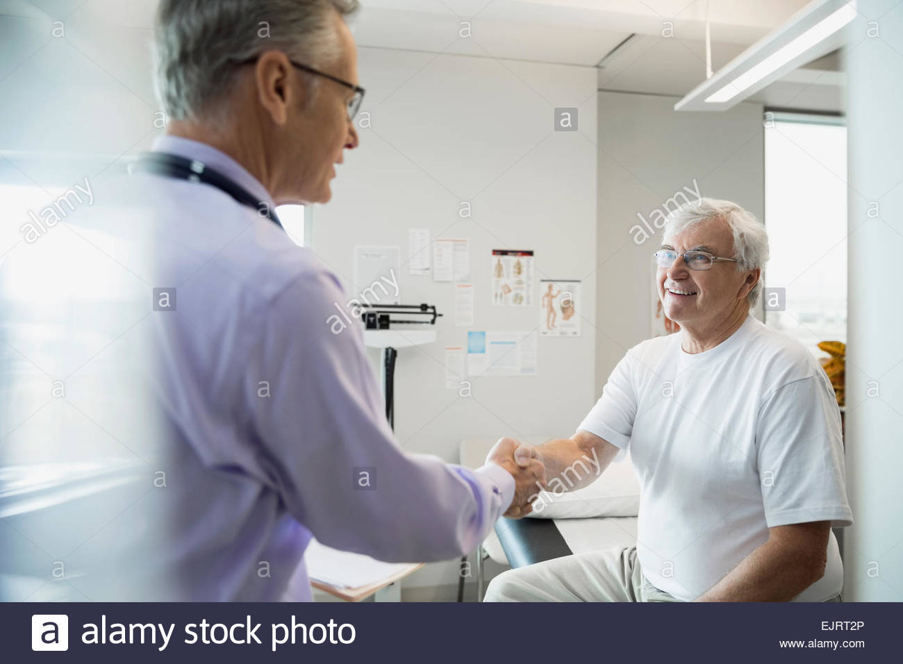 Doctor handshaking with senior man in examination room - Stock Image