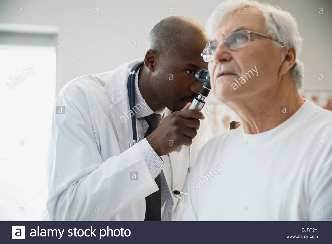 Doctor checking senior mans ear with otoscope Stock Photo