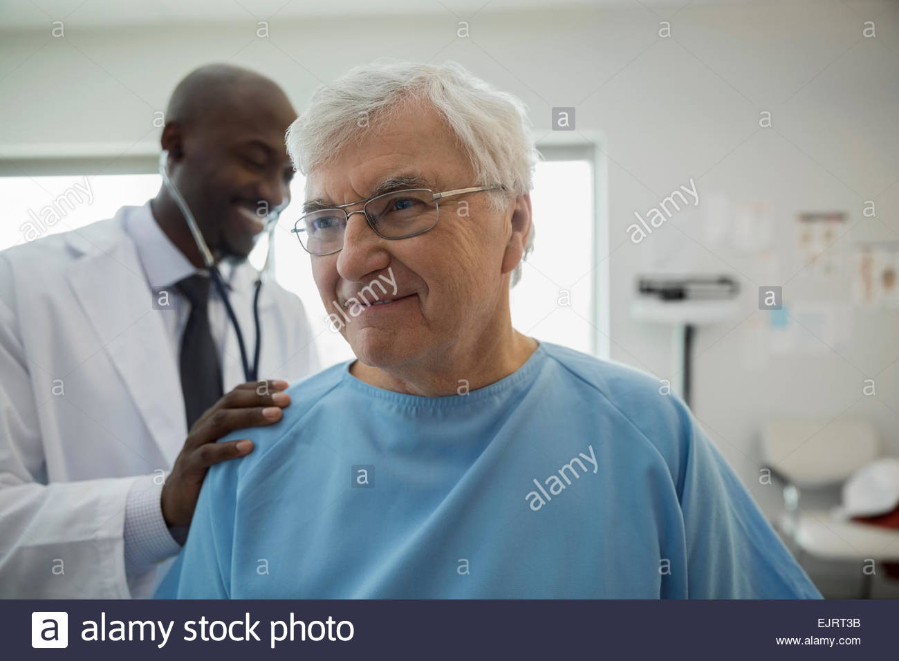 Doctor checking senior mans back in examination room Stock Photo
